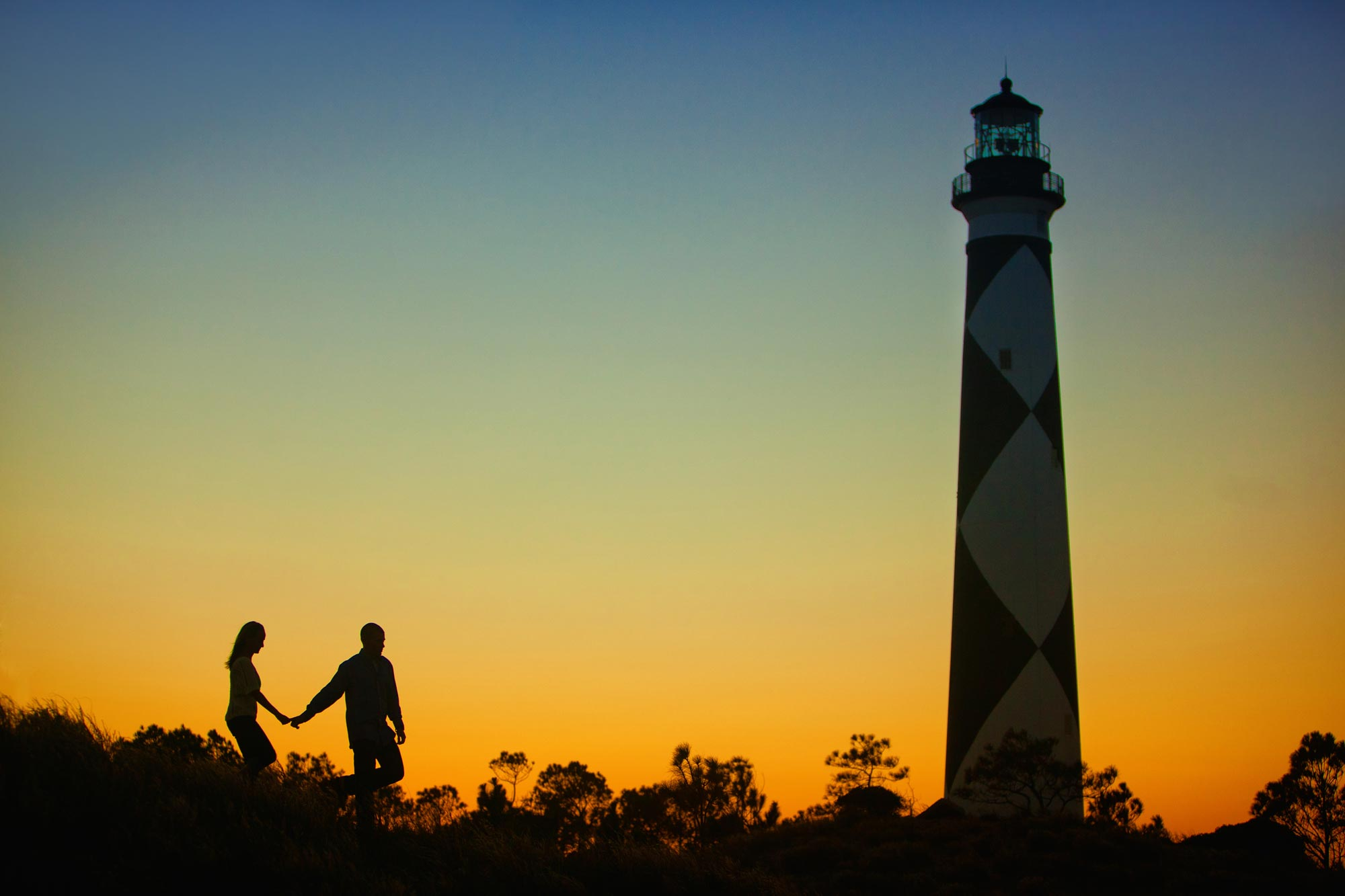 sunset silhouette of couple at Cape Lookout NC with Lighthouse