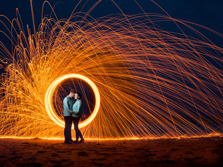 steel wool engagement picture on beach at night with long exposure