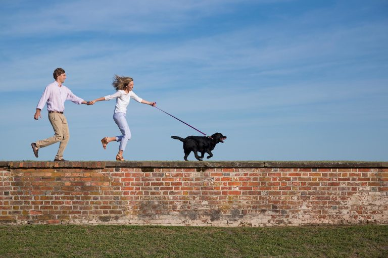 couple running with dog on wall of Fort Macon during engagement picture session
