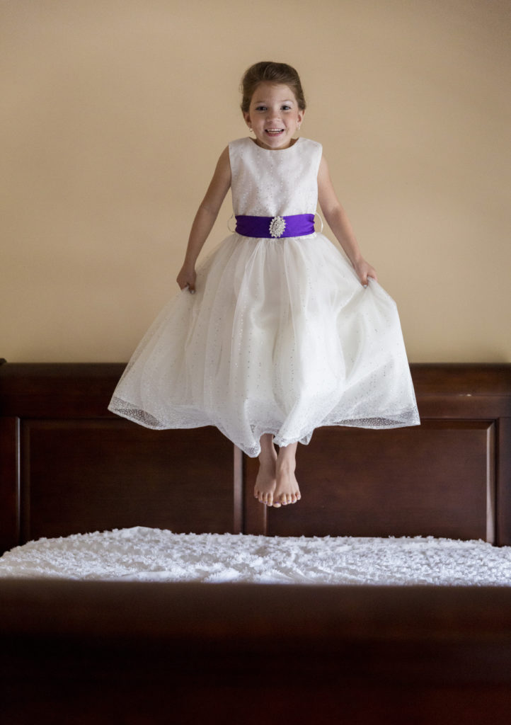 flower girl jumping on bed