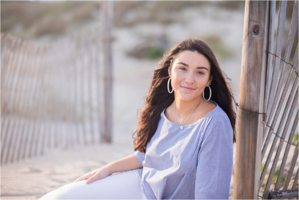 High School senior sitting by sand fence in Emerald isle
