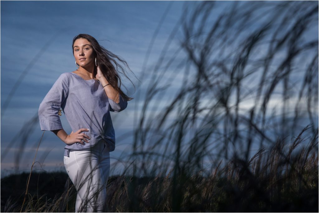 dramatic senior portrait in tall grass