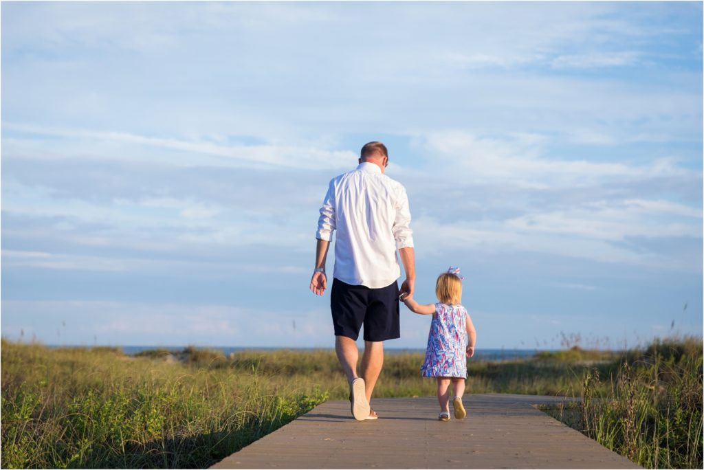 Father and toddler daughter walking to the beach