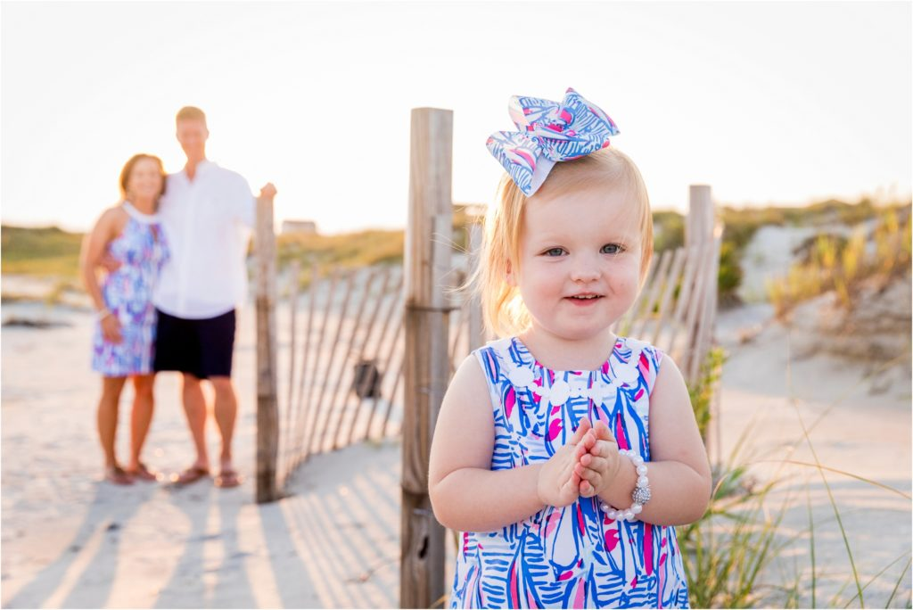 Young girl on beach with parents in the background in Emerald Isle