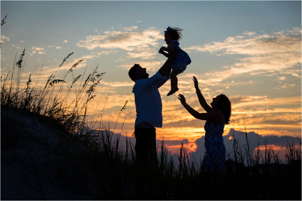 silhouette of dad tossing child into air in beach dunes in Emerald Isle NC