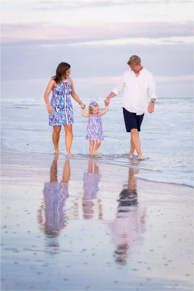 small family walking along beach