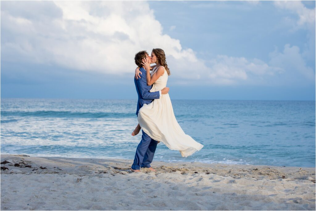 Bride in grooms arms on beach